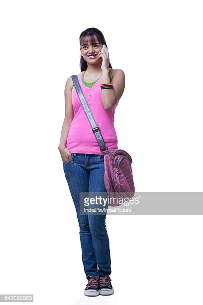 Full length of beautiful college girl using cell phone over white background
