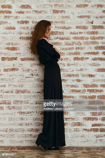 full length of beautiful woman in black dress standing against brick wall - black dress stock pictures, royalty-free photos & images