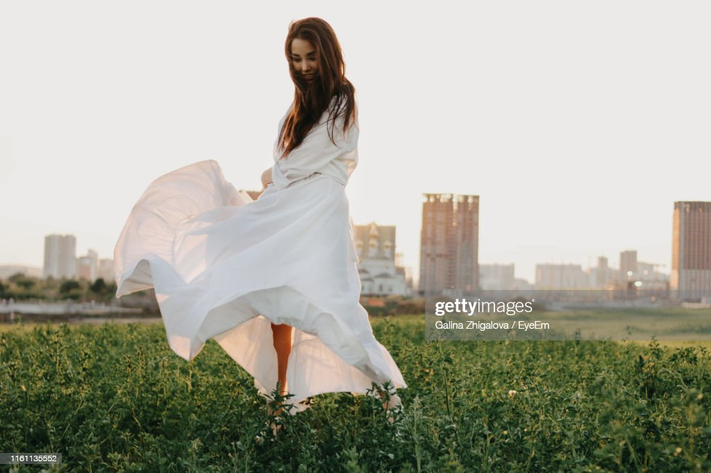 Full Length Of Beautiful Woman In White Dress Waking On Land In City Against Clear Sky During Sunset : Stock Photo