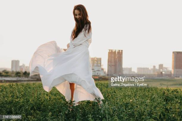 full length of beautiful woman in white dress waking on land in city against clear sky during sunset - kleid stock-fotos und bilder
