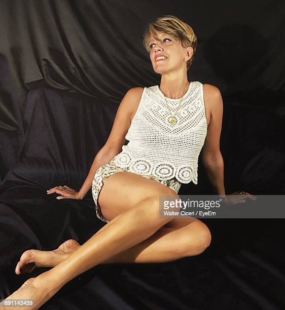 full length of beautiful woman sitting on black fabric - walter ciceri foto e immagini stock
