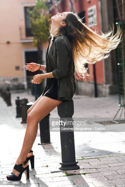full length of beautiful woman sitting with tousled hair on bollard at walkway - tacchi alti foto e immagini stock