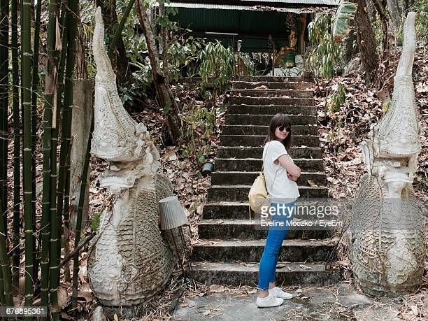 Full Length Of Beautiful Woman Standing By Steps At Buddhist Temple