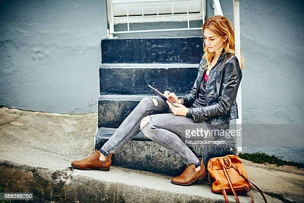 full length of beautiful woman using digital tablet on steps - calzature di pelle foto e immagini stock