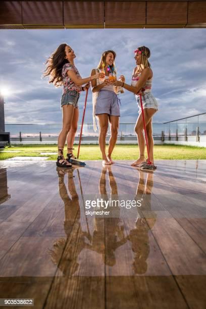 Voller Länge von schönen Frauen Toasten mit Cocktails auf einer Penthouse-Terrasse.