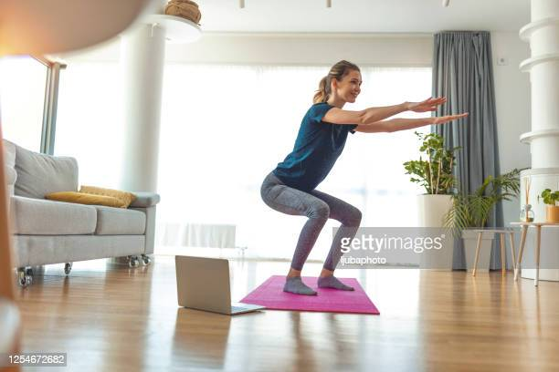 full length of beautiful young woman in sports clothing crouching while exercising at home - crouching stock pictures, royalty-free photos & images