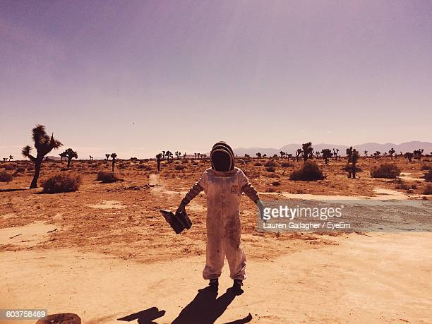 Full Length Of Beekeeper Standing In Desert Against Sky