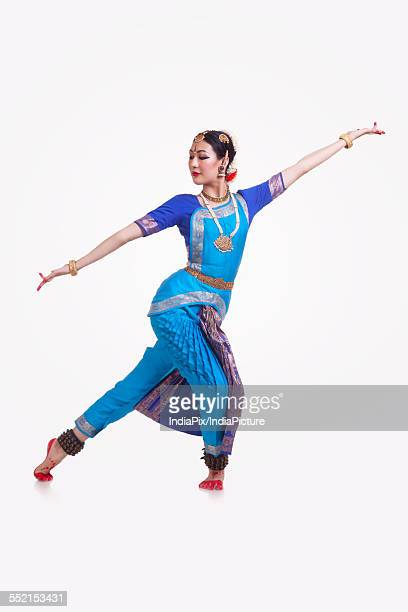 Full length of Bharat Natyam dancer performing over white background
