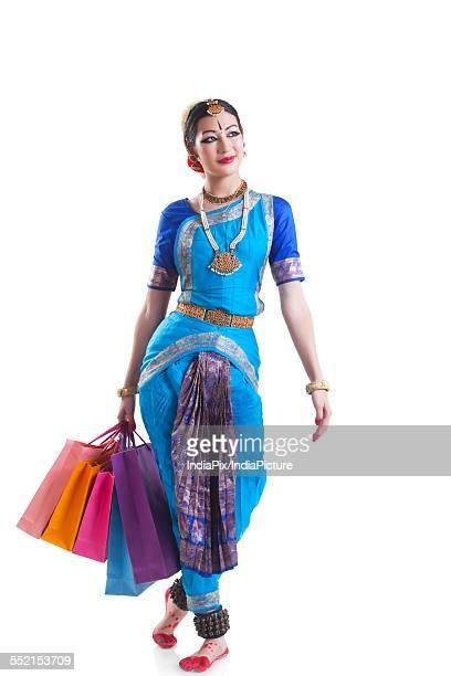 Full length of Bharatanatyam dancer carrying shopping bags over white background