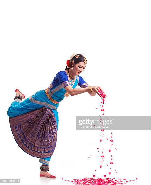 Full length of Bharatanatyam dancer dropping rose petals over white background