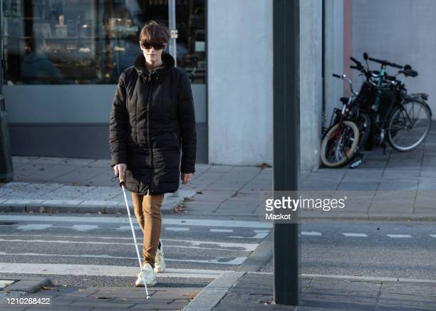 full length of blind woman crossing road with stick in city - 視覚障害 ストックフォトと画像
