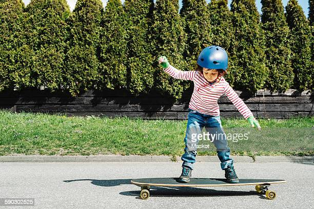 Full length of boy balancing on skateboard at yard