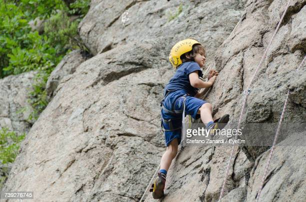 Full Length Of Boy Climbing Cliff