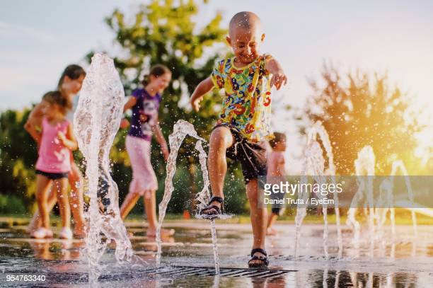 full length of boy enjoying on fountain against sky - fountain stock pictures, royalty-free photos & images