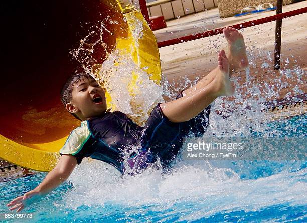 Full Length Of Boy Enjoying On Water Slide In Pool