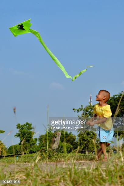 Full Length Of Boy Flying Kite Over Field Against Clear Blue Sky