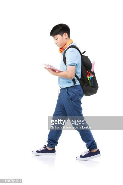 full length of boy holding books while walking on white background - people stock pictures, royalty-free photos & images