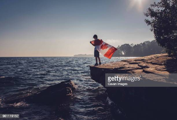 full length of boy holding canadian flag while standing on cliff against sea and sky during sunny day - kingston ontario stock photos and pictures