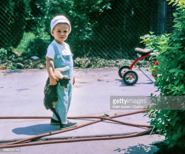 Full Length Of Boy Holding Cat While Standing In Yard