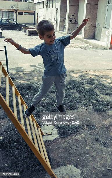 Full Length Of Boy Jumping From Ladder Against Building