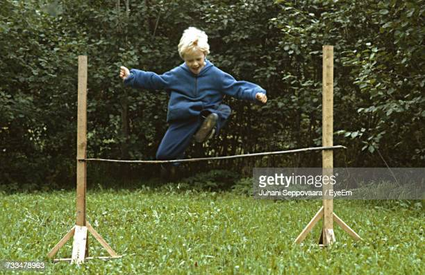 Full Length Of Boy Jumping Over Hurdle On Grassy Field