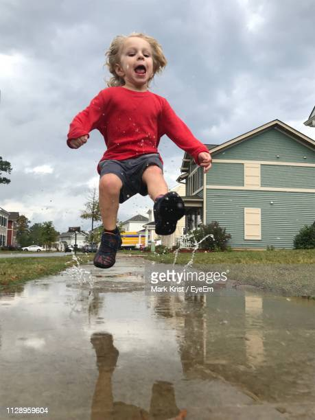 Full Length Of Boy Jumping Over Puddle Against Sky