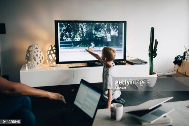 full length of boy kneeling while touching smart tv in living room at home - televisión fotografías e imágenes de stock
