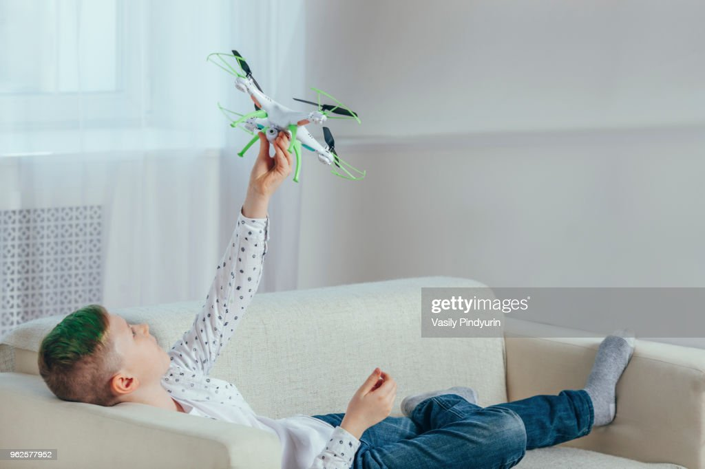 Full length of boy lying on sofa holding drone at home : Stock Photo