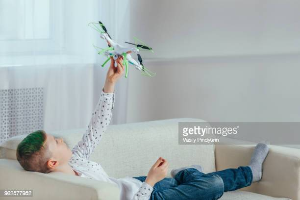 Full length of boy lying on sofa holding drone at home
