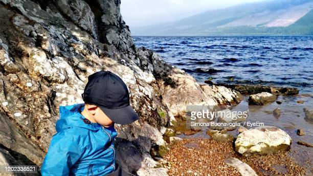 full length of boy on rock at beach - extreme terrain stock pictures, royalty-free photos & images