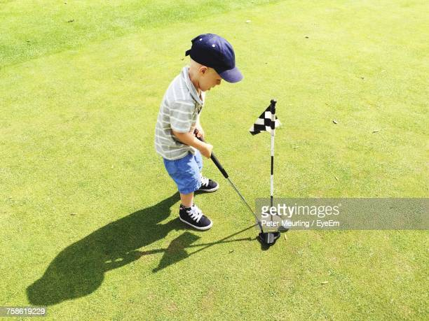 full length of boy playing on golf course - miniature golf stock photos and pictures