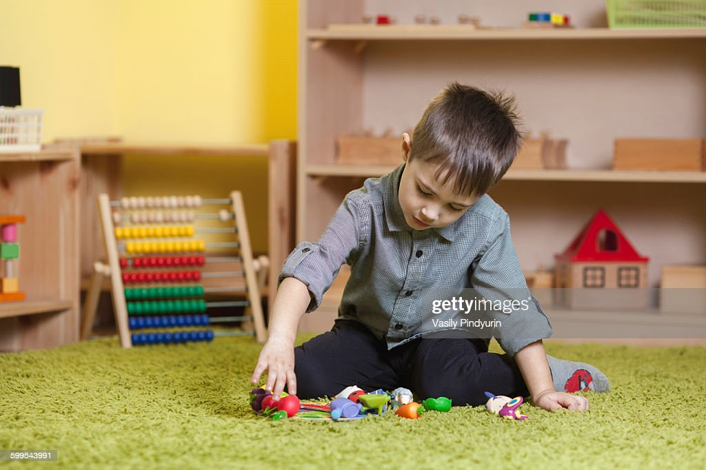 Full length of boy playing with toys on rug in classroom : Stock Photo