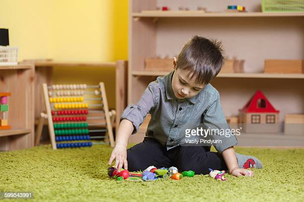 Full length of boy playing with toys on rug in classroom