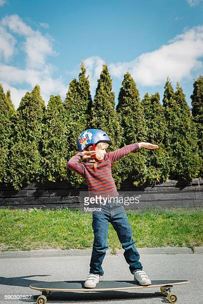 Full length of boy posing while standing on skateboard at yard