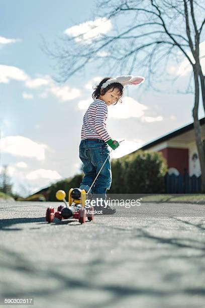 Full length of boy pulling toy car on footpath at yard