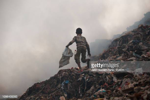 full length of boy running on garbage dump against sky - チッタゴン ストックフォトと画像