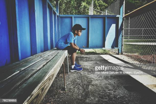 full length of boy sitting on bench - ausschluss stock-fotos und bilder
