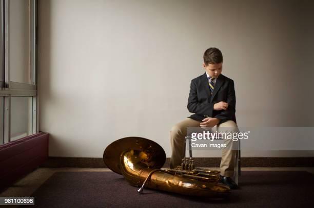 Full length of boy sitting on chair by tuba on floor