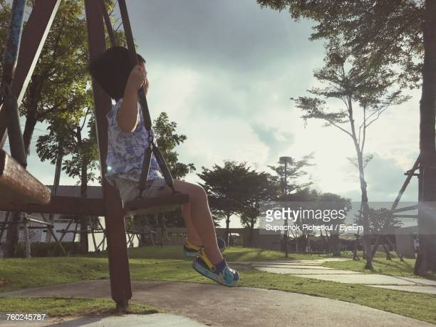 Full Length Of Boy Sitting On Swing At Playground