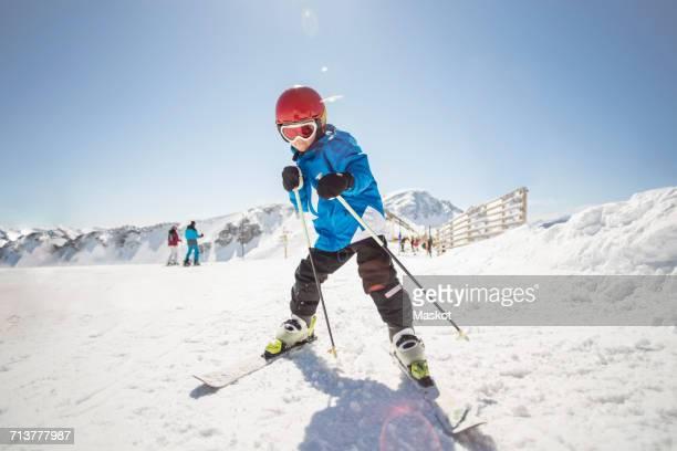 Full length of boy skiing on snow covered field against clear sky