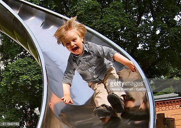Full length of boy sliding down slide on playground