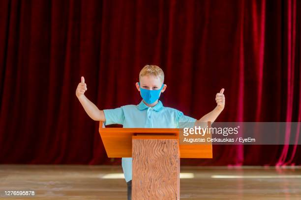 full length of boy standing against curtain - winners podium stockfoto's en -beelden