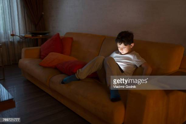 Full length of boy using digital tablet while sitting on sofa at home