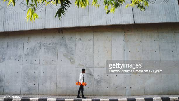 full length of boy walking on footpath against wall - fortified wall stock pictures, royalty-free photos & images