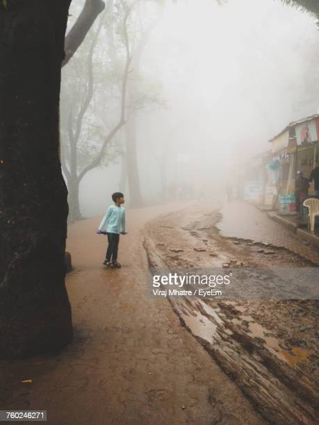 Full Length Of Boy Walking On Footpath During Foggy Weather