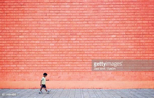 Full Length Of Boy Walking On Sidewalk Against Wall