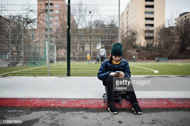 full length of boy wearing warm clothing while using mobile phone against soccer field in city - alleen jongens stockfoto's en -beelden