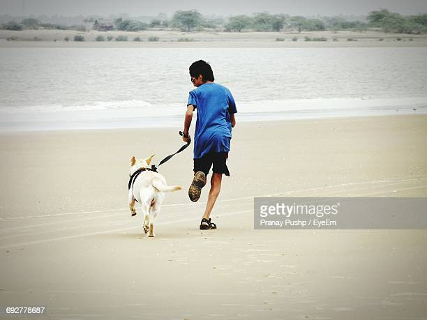 Full Length Of Boy With Dog Running At Beach
