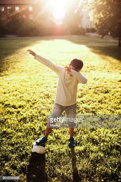 Full length of boy with soccer ball covering face while standing on grassy field at park
