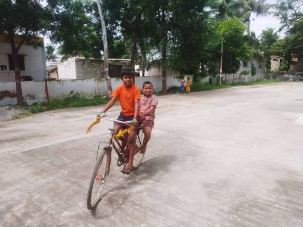 Full Length Of Boys Riding Bicycle On Road